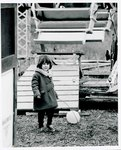 "F09_E06_02 Little girl standing in front of the ferris wheel set for ""The Learning Tree"" on location in Bourbon and Linn counties, Kansas by Unknown"