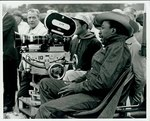 "Gordon Parks sits behind a movie camera on location for ""The Learning Tree"" in Bourbon and Linn counties, Kansas (2) by Norman E. Tanis"